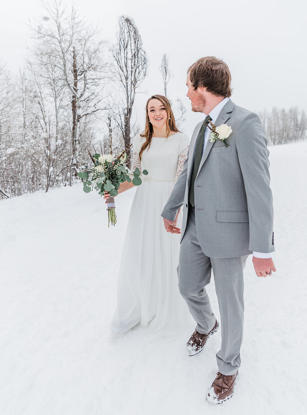 future man and wife walking hand in hand through the snow beautiful winter day walking through tony's grove in cache valley utah utah picture locations beautiful grove rustic country wedding everything covered in snow inspiration for wedding pictures #winterwedding #formals #tony'sgrove #cachevalley #snowcoveredtrees #bellaalderphotography #professionalphotographer #winterwonderland #couplegoals #weddingattire
