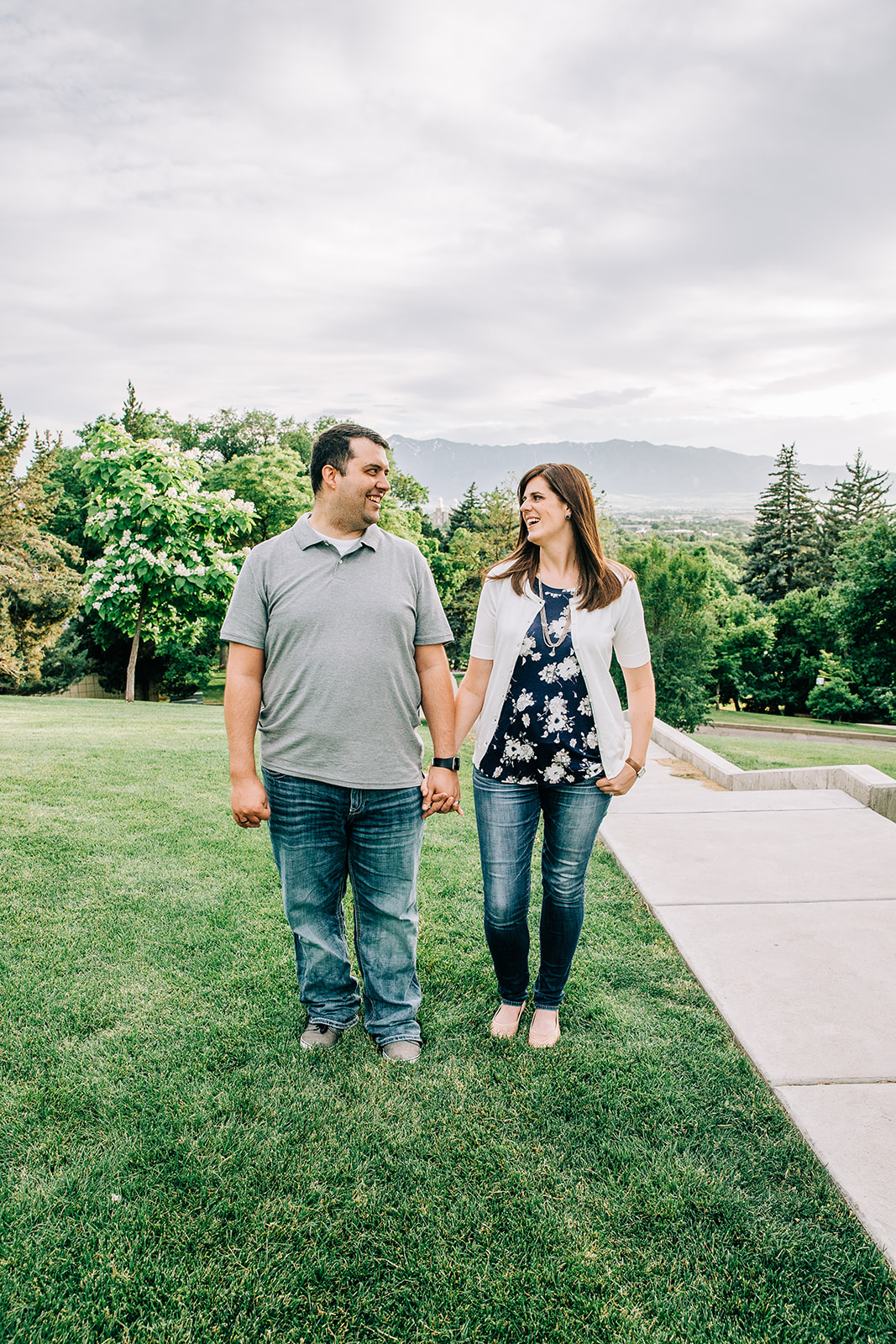 Engagement pictures happy couple holding hands walking on a college campus professional engagement photos by Bella Alder Photography available for travel around Northern Utah #bellaalderphoto #engagements #ldsengagements #engagementsession #engagementphotographer #ldsphotographer #loganutahphotographer