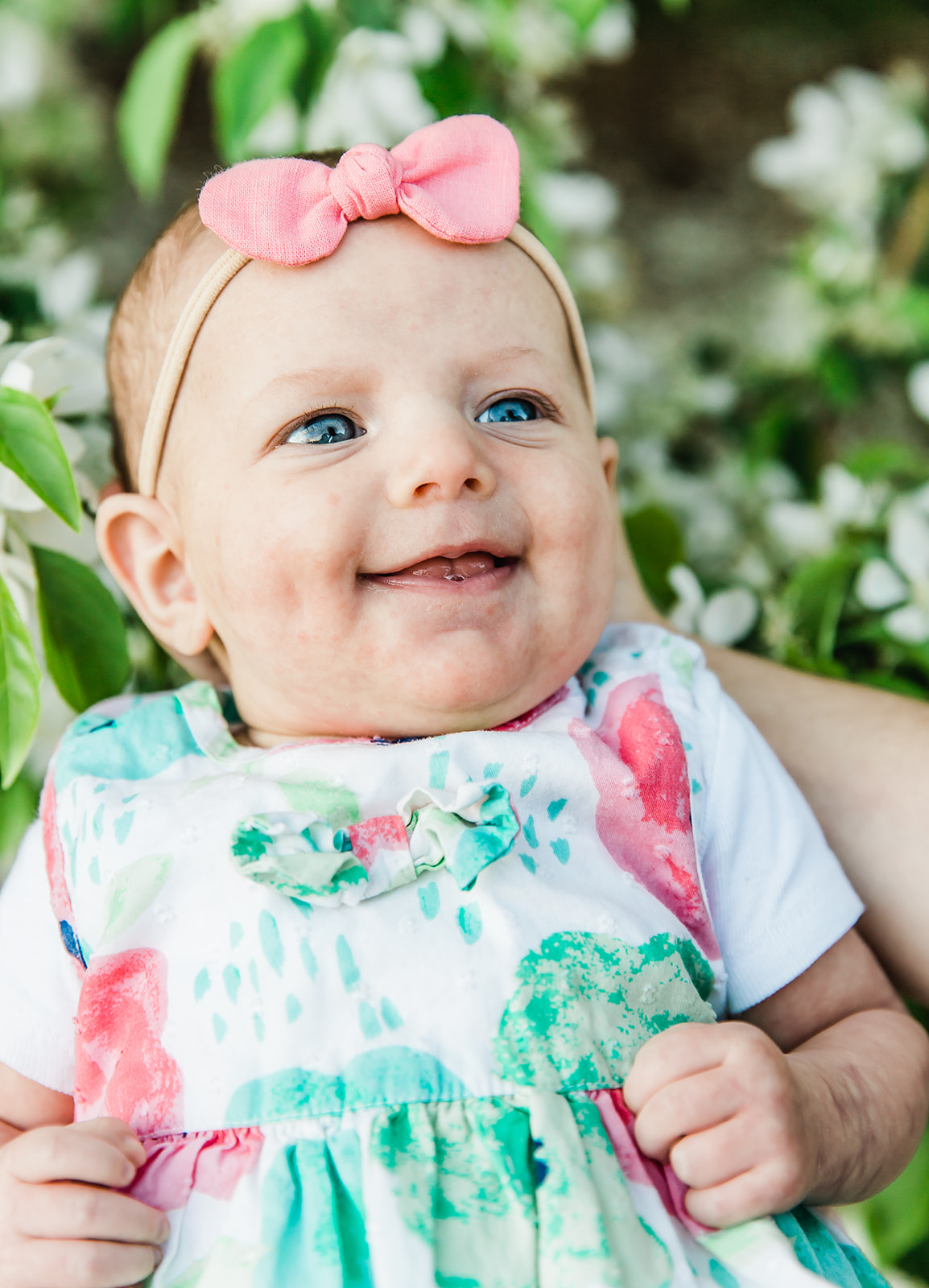 Happy baby with blue eyes. Flower baby dress. Happy girl. Big pink bow. Infant photography. Beautiful professional family photos. Big smiles from a baby girl. #blueeyes #pinkbow #infantphotography #makehersmile #happybabygirl #threeweekold #smileybaby #flowerdress #prfessionalphotos