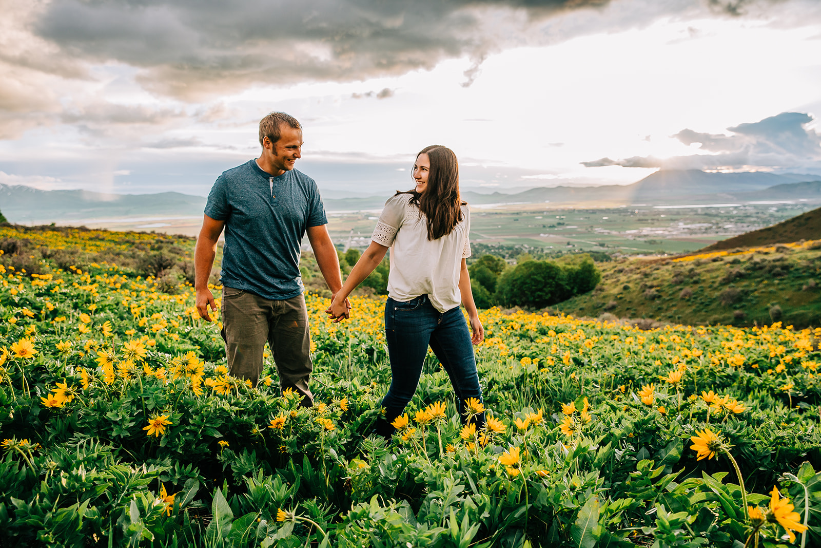 Beautiful sunflower field for photos. Mountain flowers. Mom and dad pose holding hands. Walking through a field of sunflowers. Happy families together. Holding hands walking through a field of flowers. Springtime mountain photos. Professional Family photos. #sunflowerfields #husbandandwife #mountainphotography #happyfamily #wildflowers #sunflowers #springtimephotos #momanddadphoto #familiestogetherforever