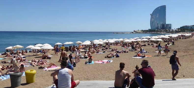 The beach in Barcelona is packed with sun-lovers, iconic W Hotel in the background