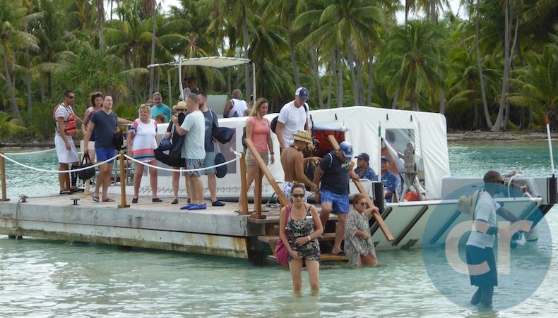 Tender drops guests off in knee-high water at Motu Mahana