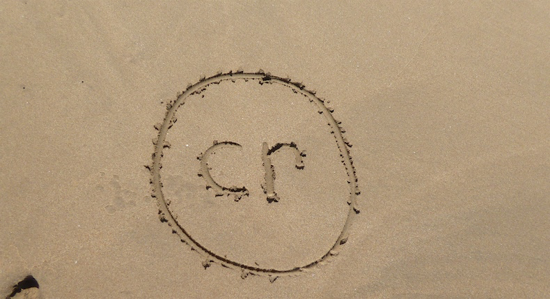 Our social media logo traced in the sand