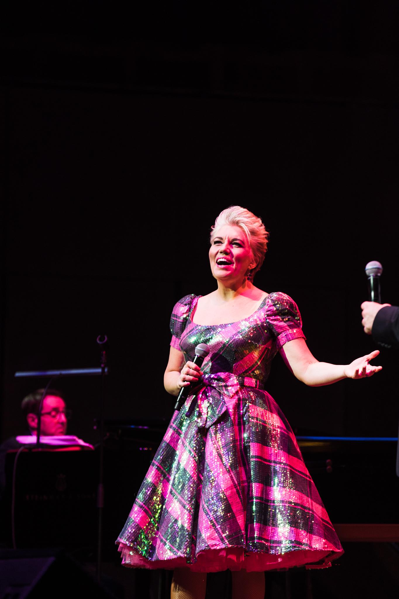 Melinda Schneider holding microphone on stage