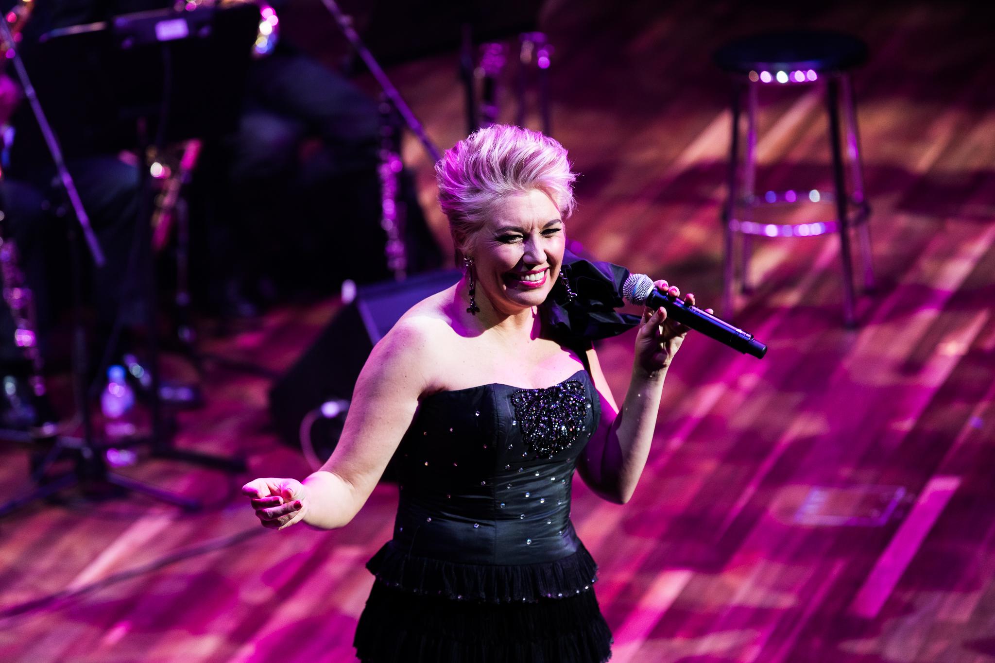Melinda Schneider singing and dancing on stage