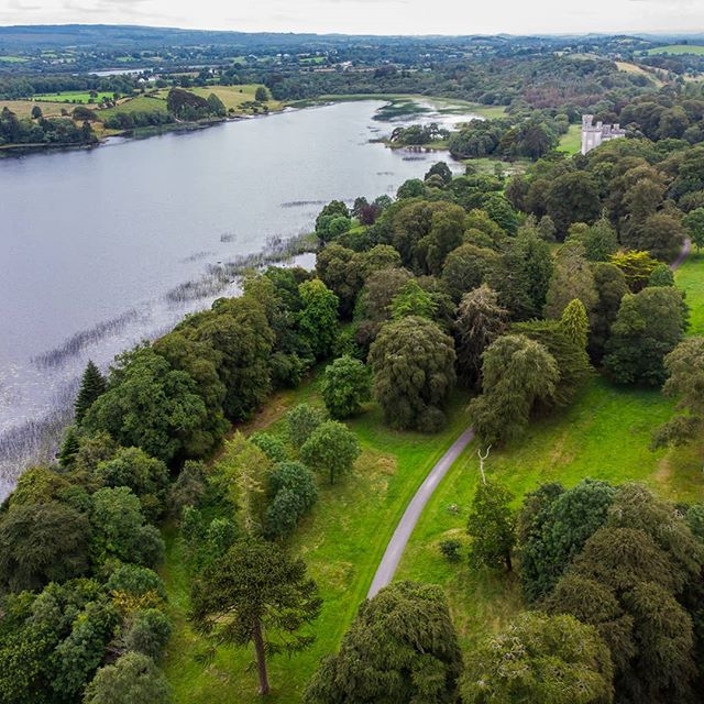 Lough Cutra Castle | Galway.  A birds eye view of the castle amongst the trees alongside the lake.