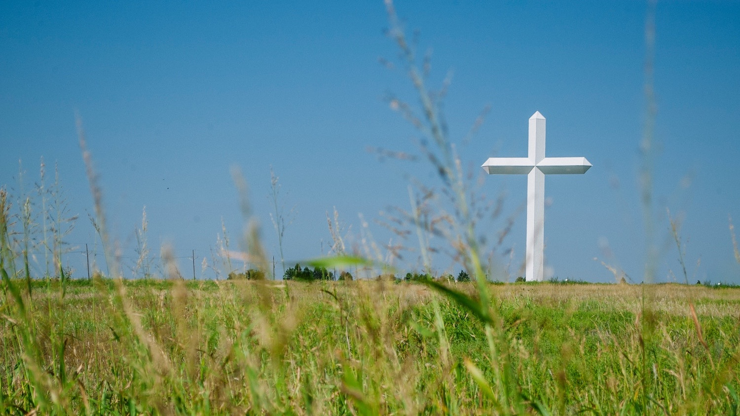 A large white cross against a blue sky in a field