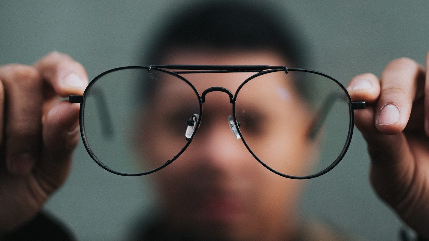 A person holding glasses, with a blurry background