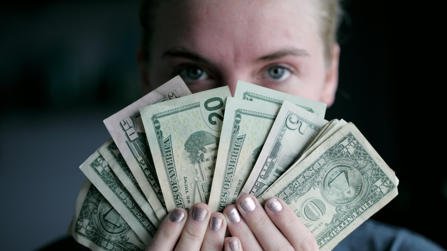 A person holding cash in front of their face