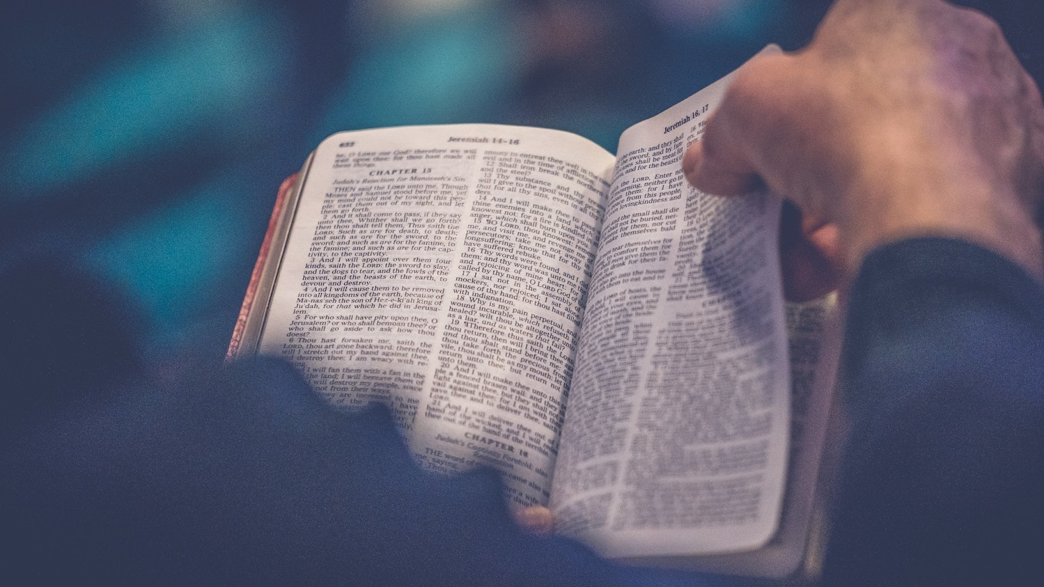 A hand turning the pages of a Bible