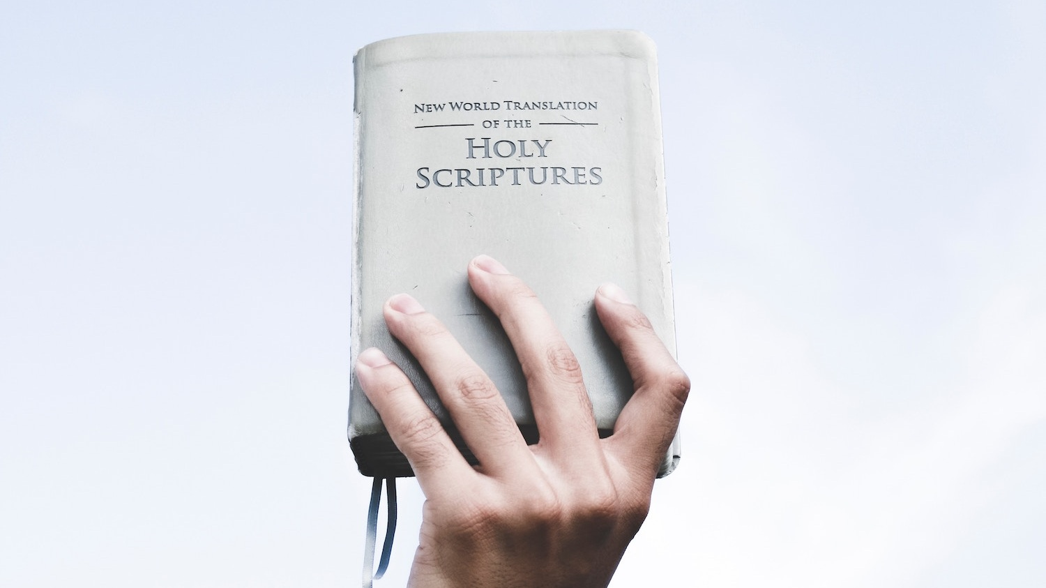 A hand holding a Bible in the air