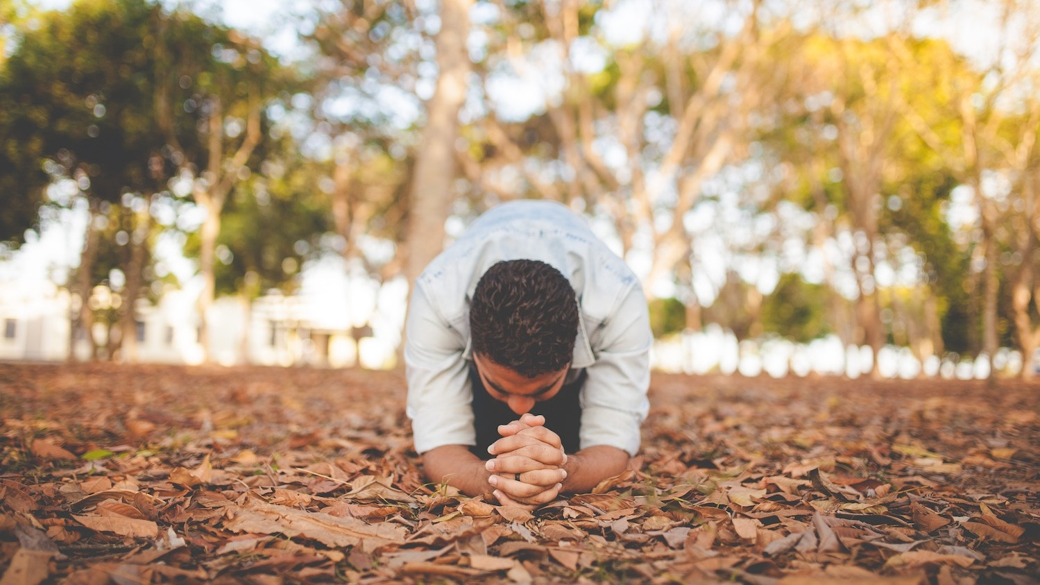 A person kneeling on the ground in prayer