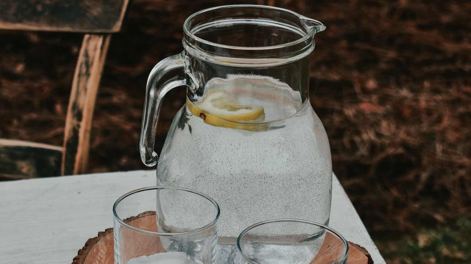 A water jug with glasses full of ice