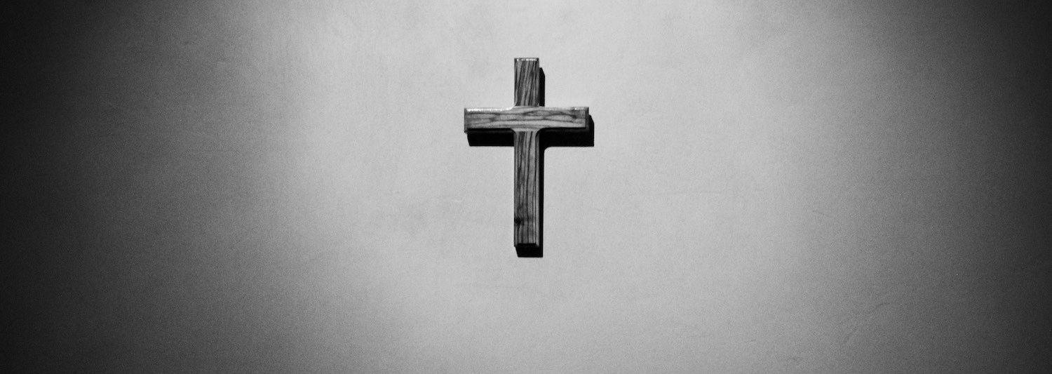 A black and white photo of a cross on the wall.