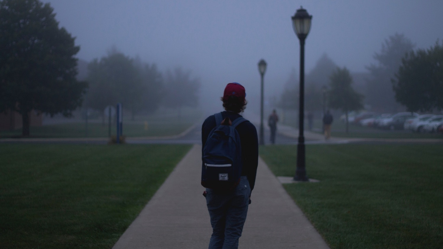 A college student on a misty sidewalk