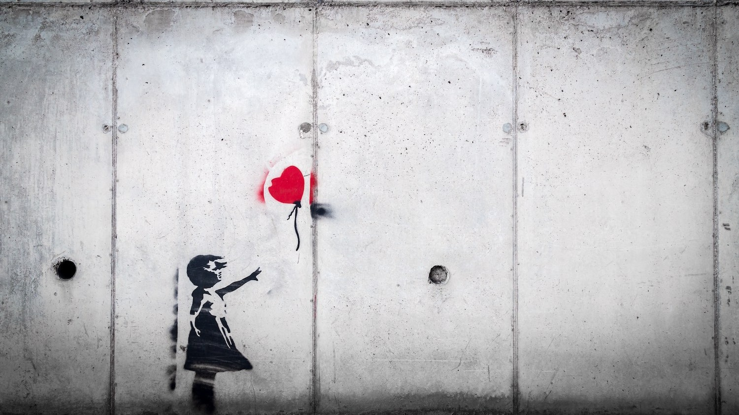 A Banksy wall graffiti of a girl reaching for a balloon that is floating away.