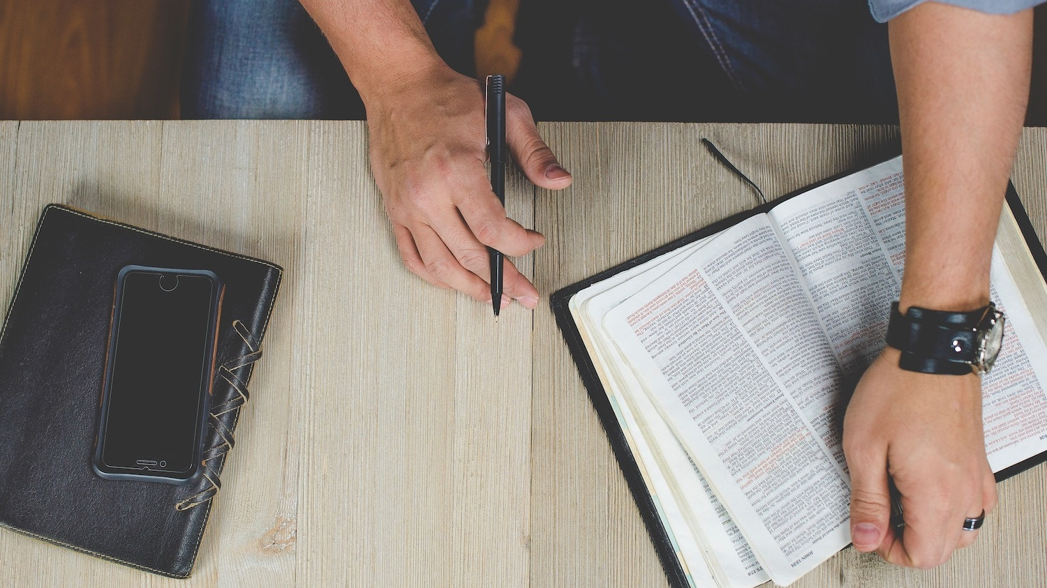 A desk with a person holding an open Bible and pen, with a phone and journal beside them