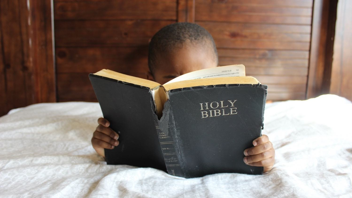A child in bed reading a Bible.