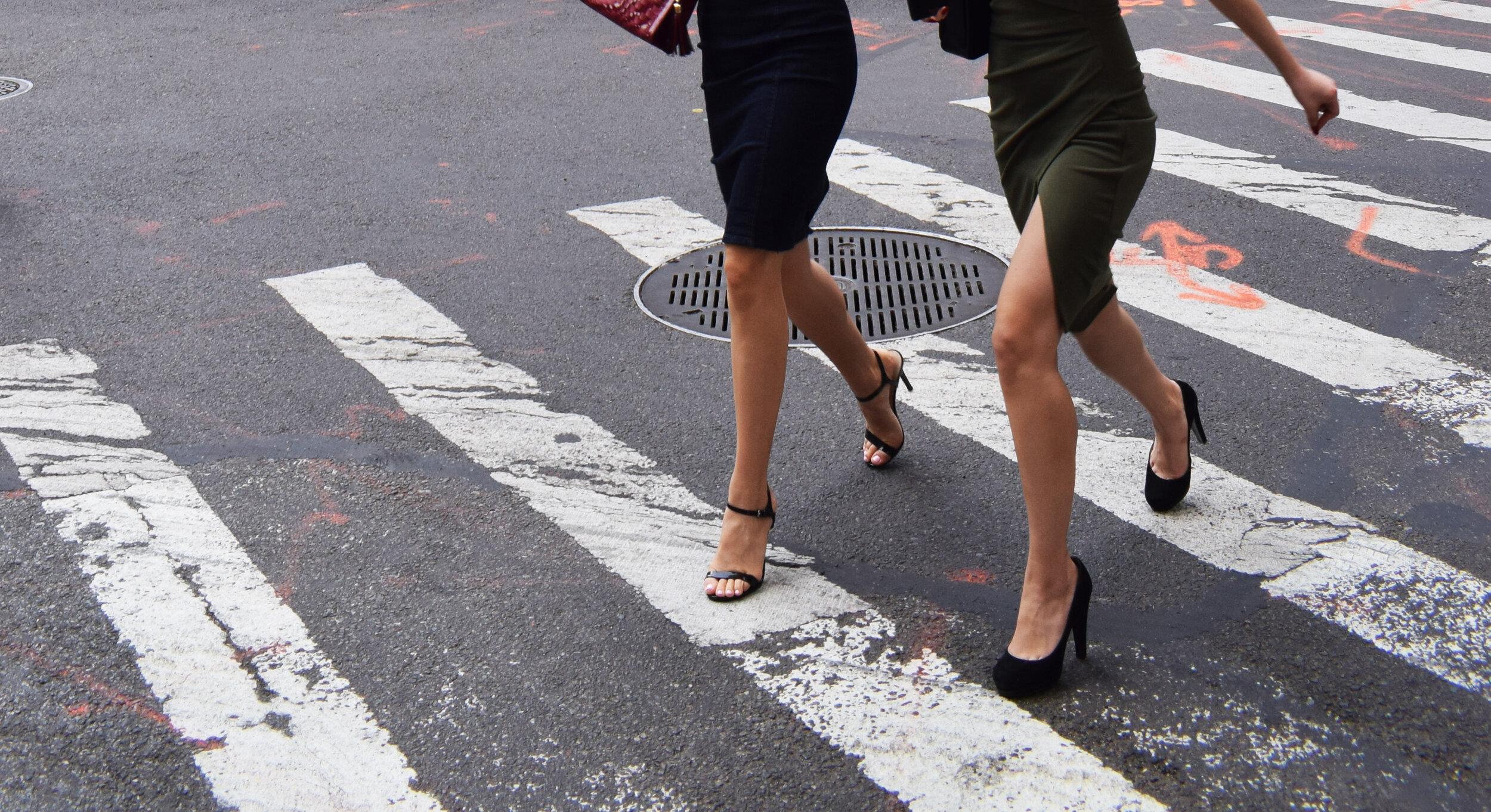Snapshot of women in professional dress crossing a street
