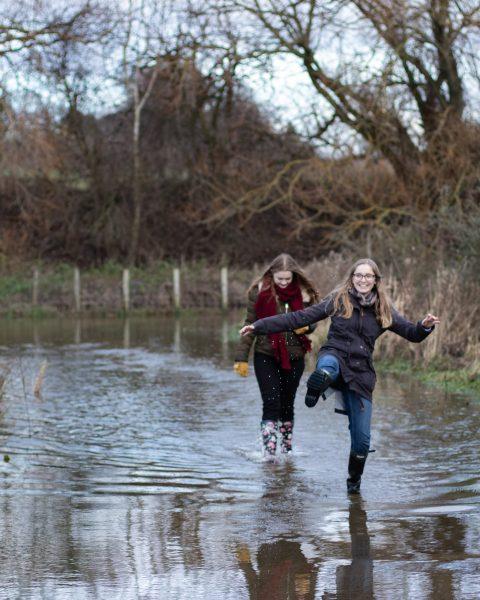 Teenage girls walking through a large puddle and kicking to splash the water