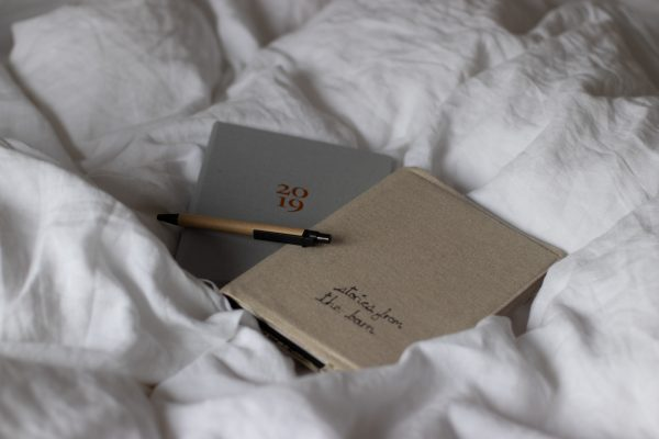 Journal and 2019 Ponderlily planner casually lying on crumpled white linen bedding