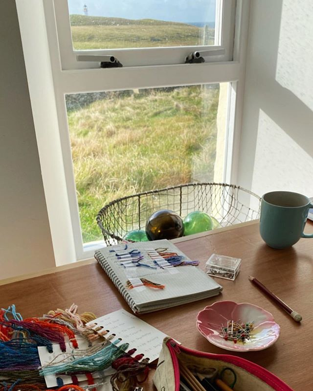 A lovely sunny work day for @mjmucklestone in the studio 💙 Mary Jane has been using her creative residency to work on a new book for her beautiful knitwear designs. What better place to do that than the birth island of Fair Isle knitting? 🐑 It's wonderful to have you with us, @mjmucklestone #fairislestudio #creativeresidency #maryjanemucklestone