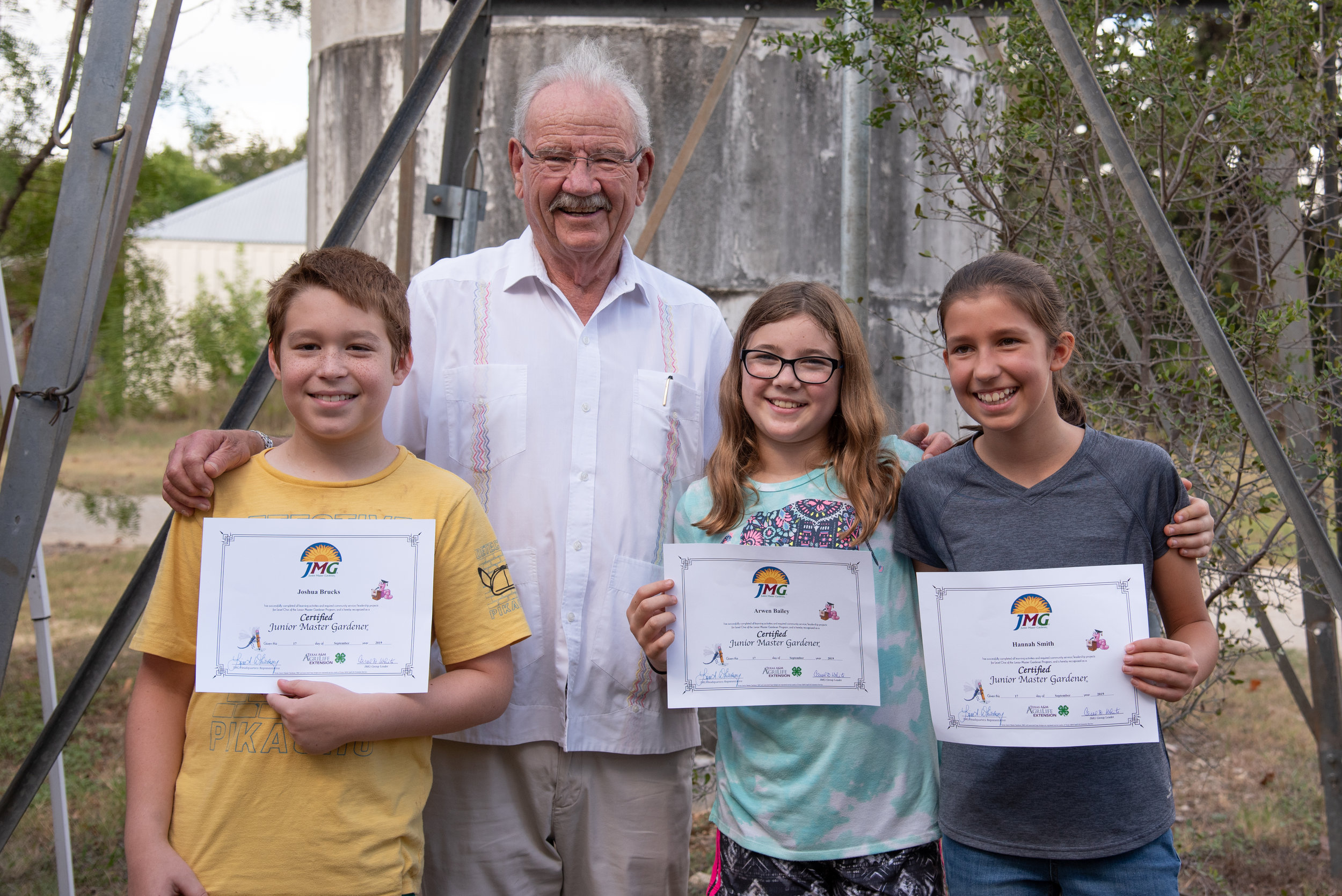Former San Antonio Mayor and park namesake, Phil Hardberger (second from left) presented the Junior Master Gardener certificates to Joshua Brucks, Arwen Bailey, and Hannah Smith on Tuesday, September 24. They are the first Children's Vegetable Gardeners in the park to earn this certification.