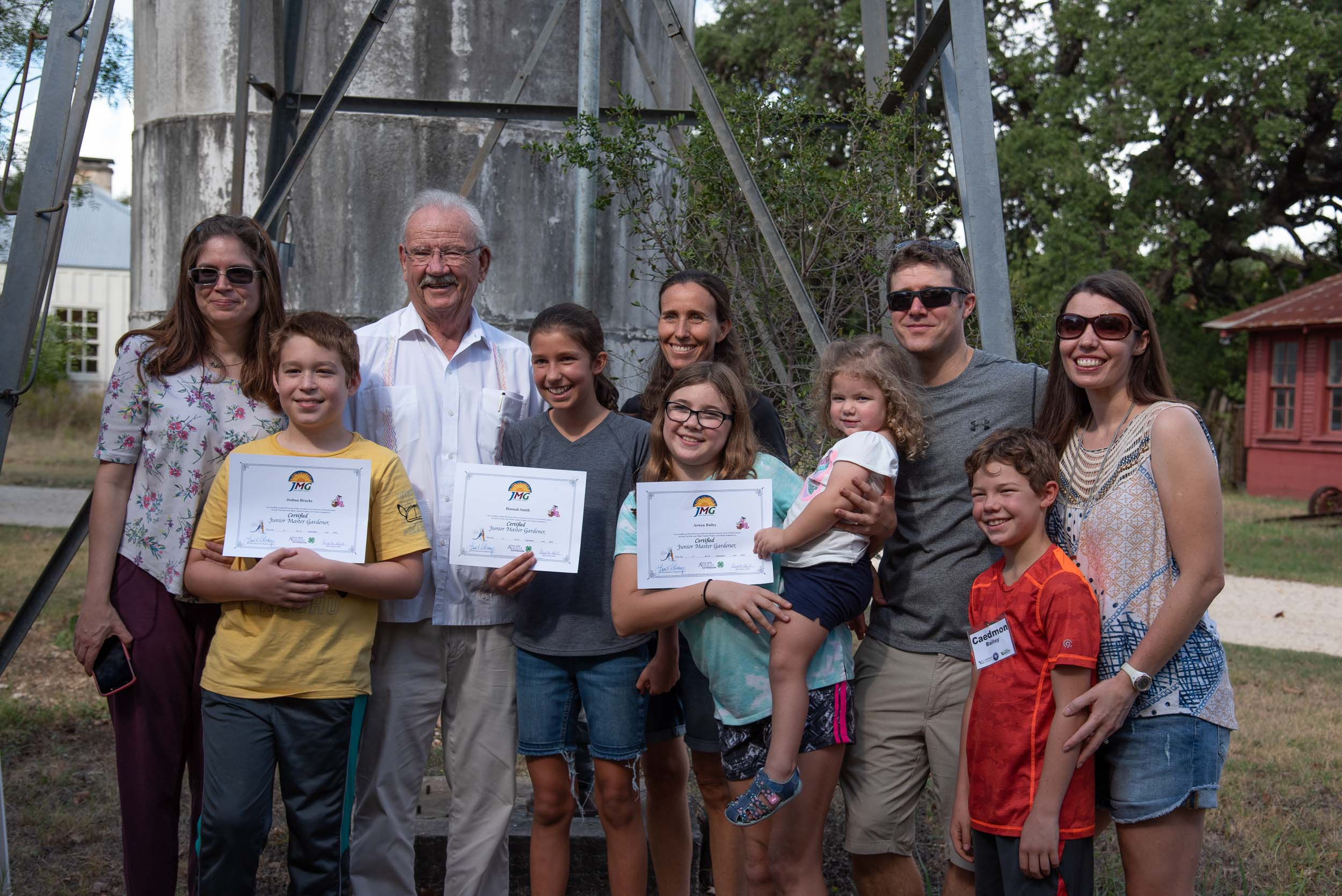 Former San Antonio Mayor and park namesake, Phil Hardberger (third from the left) stands with the three Junior Master Gardeners and their families.