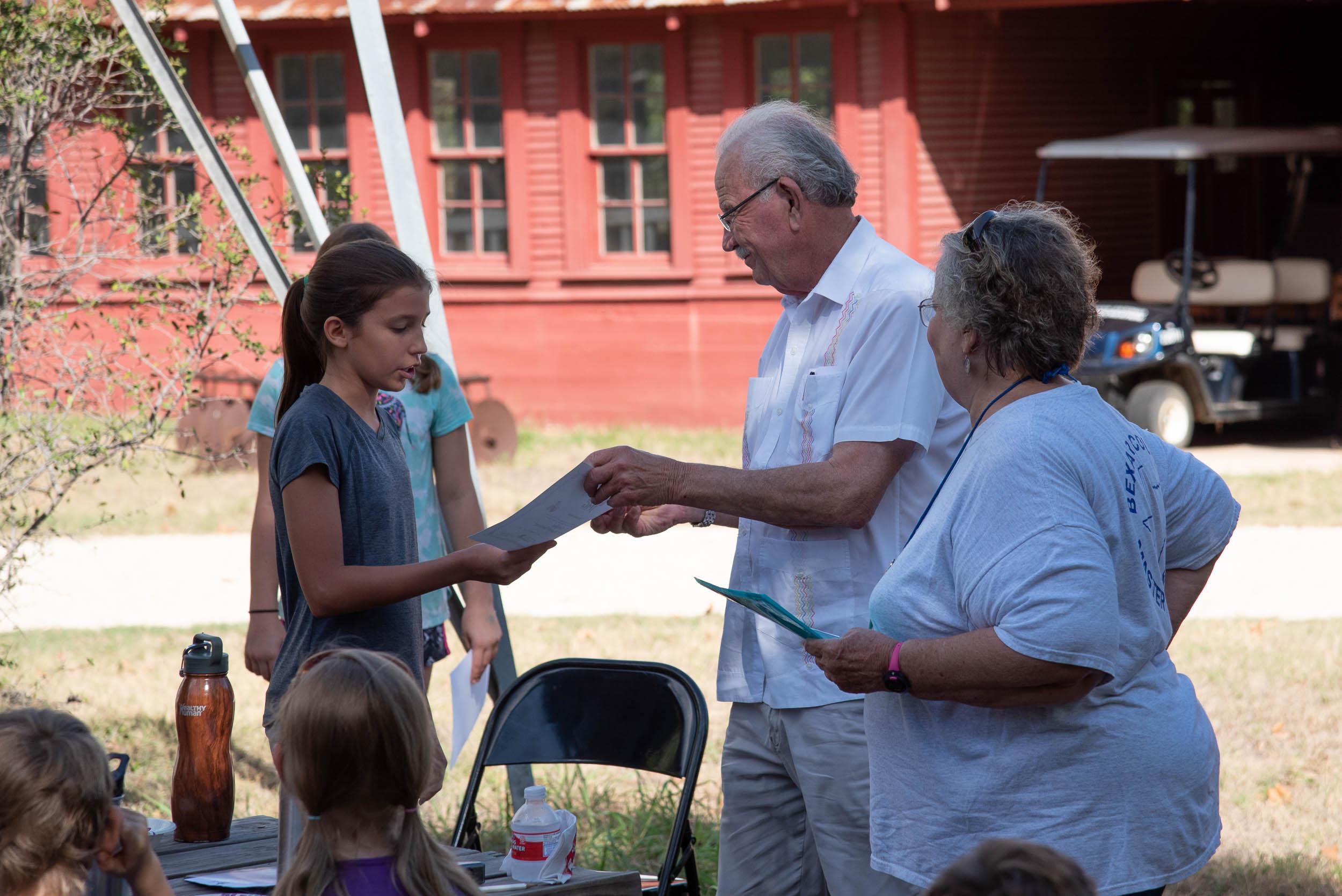 Phil Hardberger presents Hannah Smith with her Junior Master Gardener Certification.
