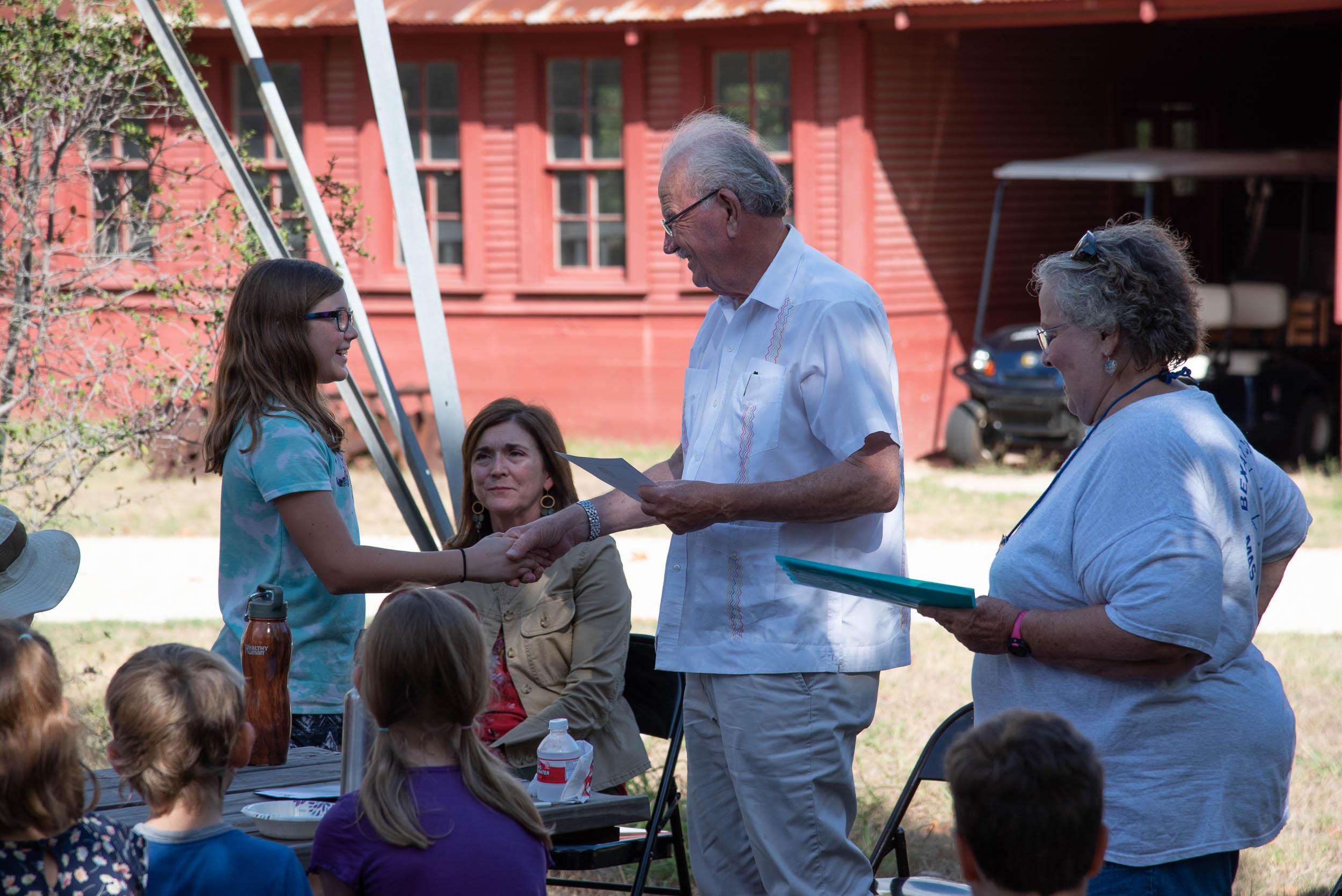 Phil Hardberger presents Arwen Bailey with her Junior Master Gardener Certification.