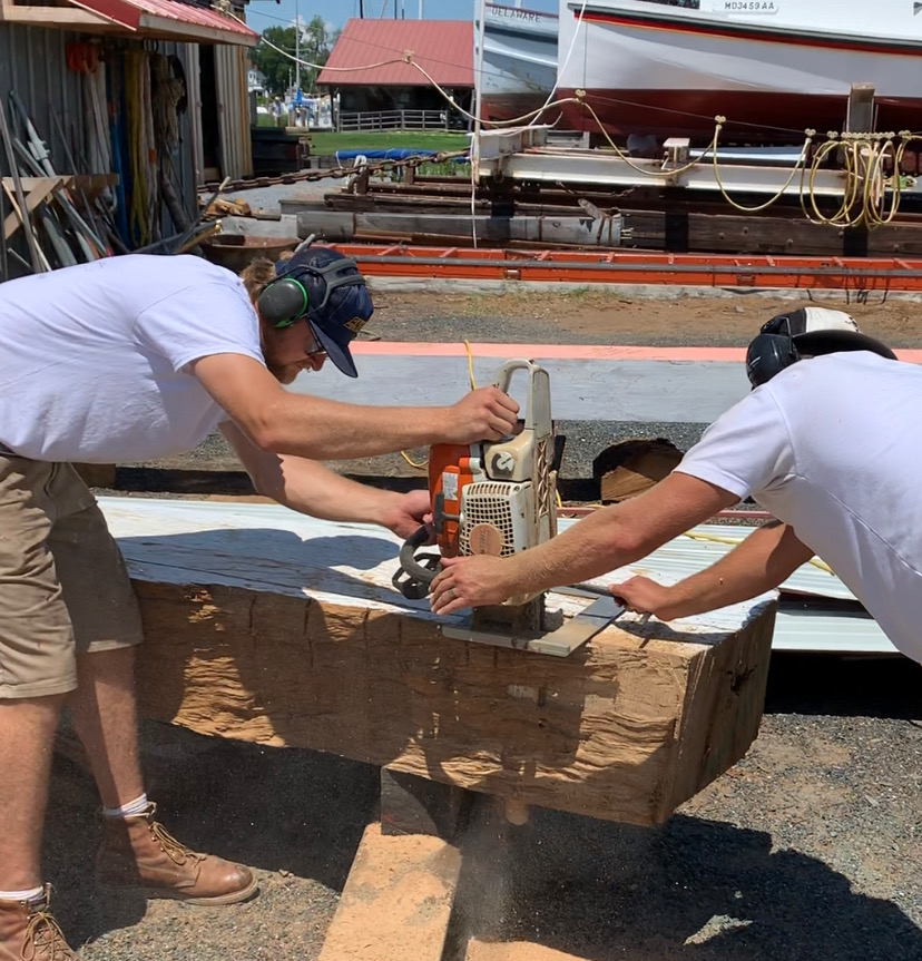 Shipwright Cole Myerhoff and Lead Joe Connor using the bigfoot chainsaw to cut out the lower gripe.