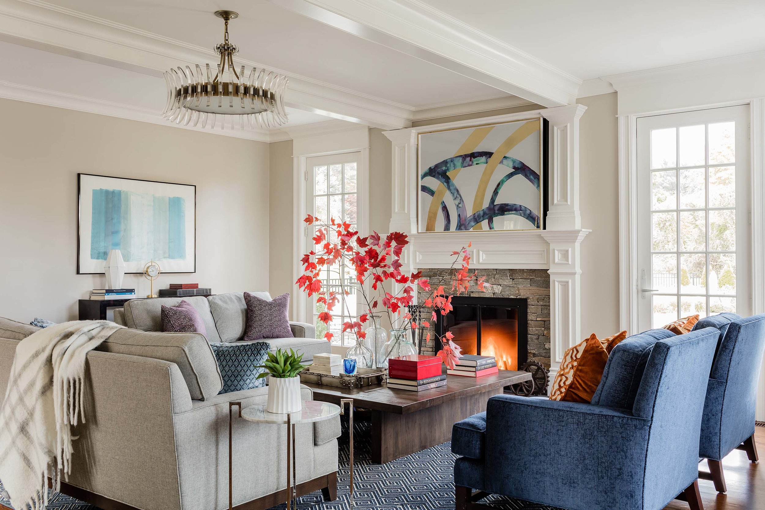 Living room with sofa, armchairs, fireplace, wooden center table, and artwork on the wall, rh, restoration hardware, verranzano bookcase, wood bookcase, kravet, pelham chair, currey and co, currey, coquette chandelier, katie.gallery artwork, katie.gallery