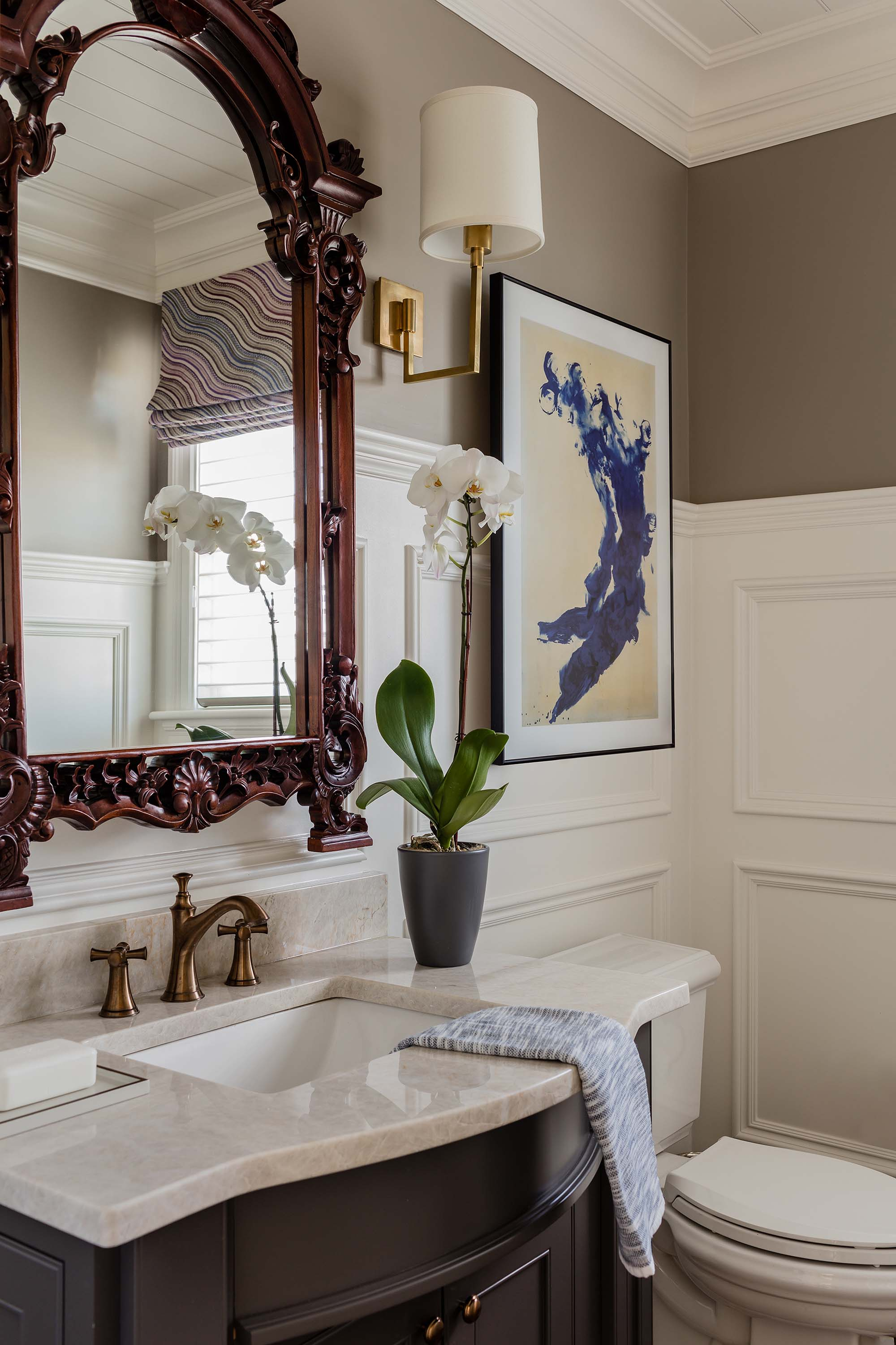 Powder room with marble sink, vintage faucet, and vintage mirror