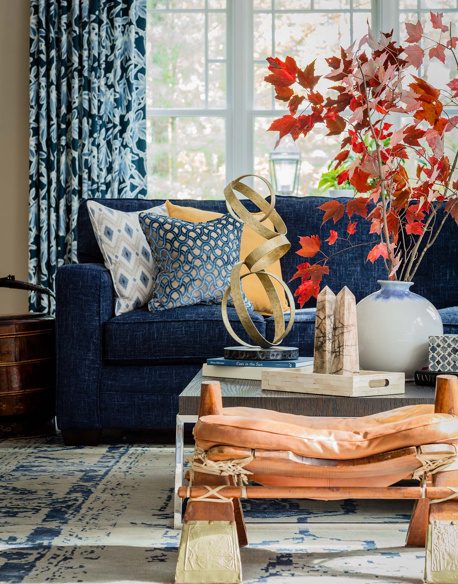 Living room with blue sofa, blue curtain and leaf branch decorations, bassett, sectional, blue velvet sectional, rh, restoration hardware, nicholas oak coffee table, camel saddle, rice pot, duralee
