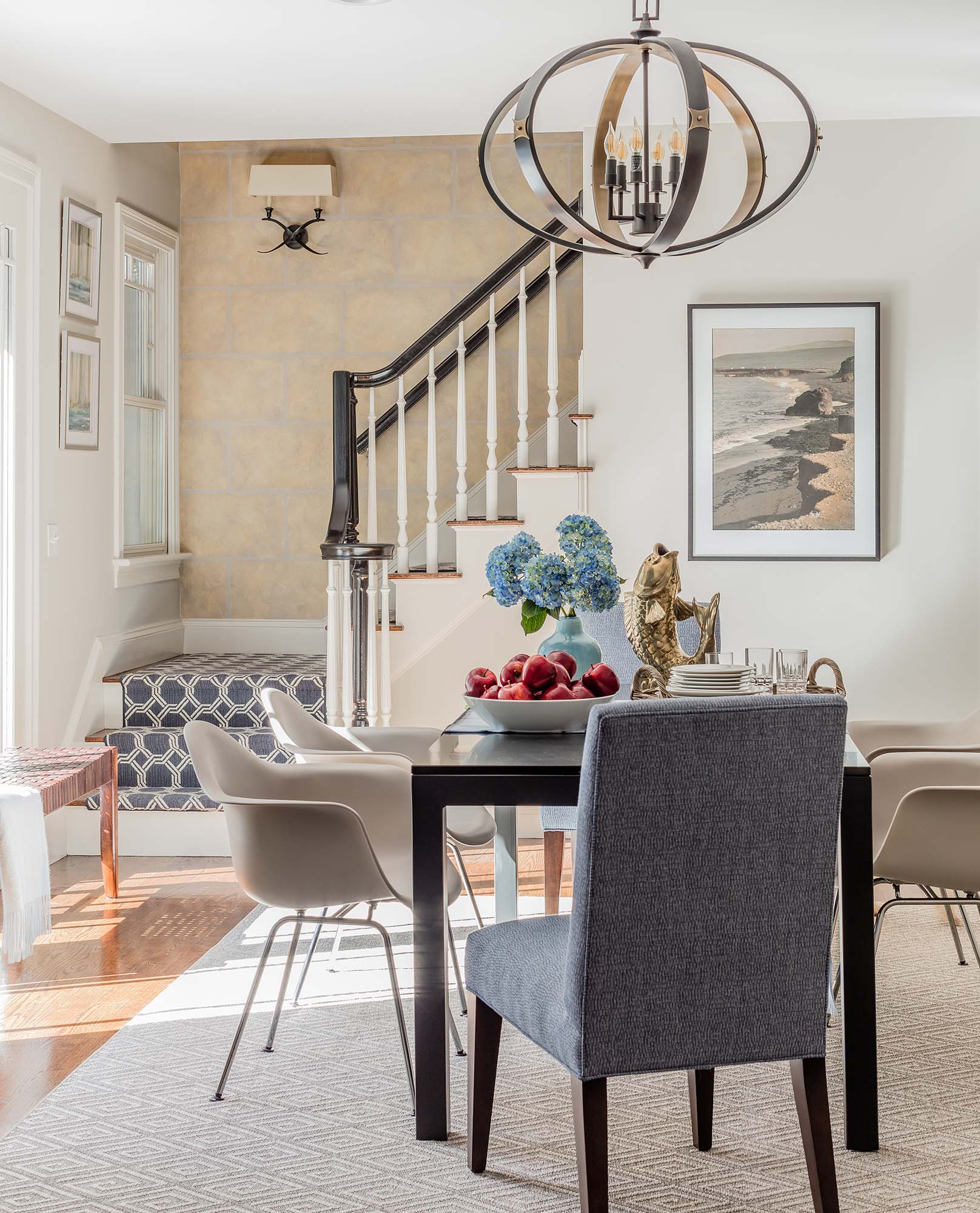 House interior with white walls, wooden table, chairs, and stairway, mitchell gold bob williams, anthony chair, eames, molded plastic chair, parsons table, parson table, currey, currey and company, huntsman, chandelier