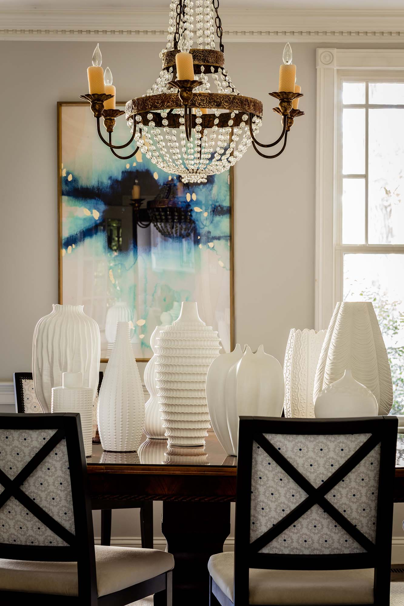 Dining room with wooden table, chairs, white modern style vases and unique style chandelier