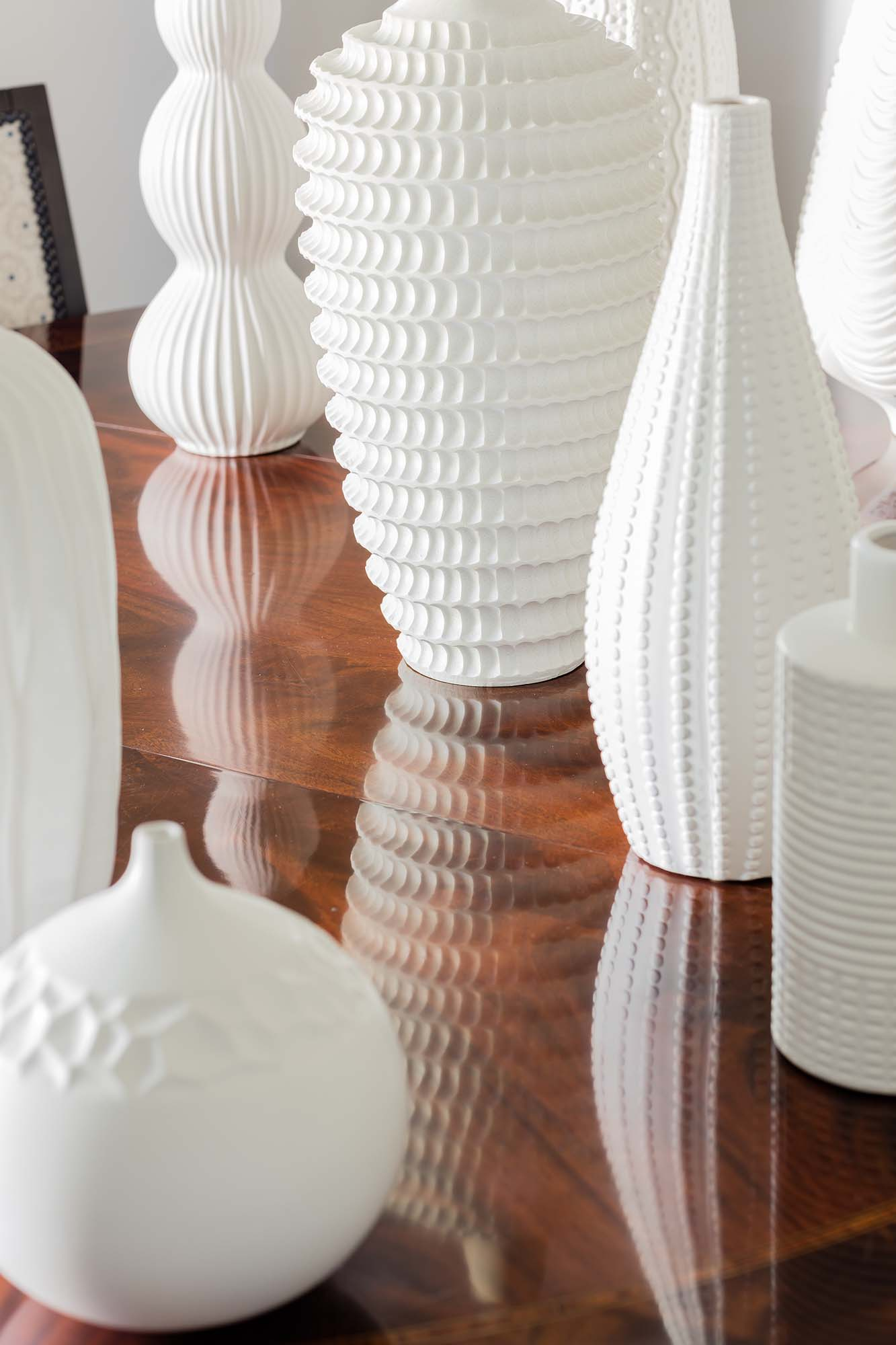 Polished wooden table with white modern vases