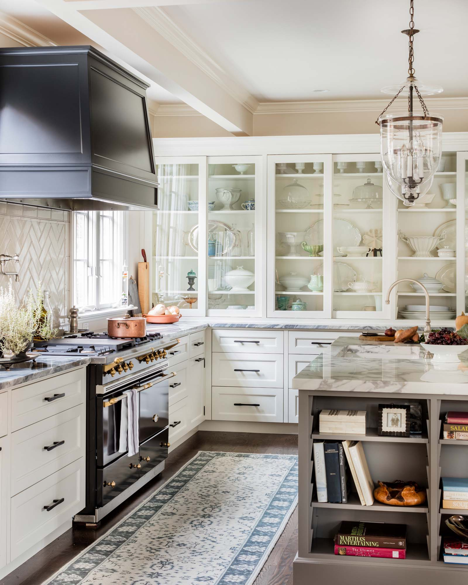 Kitchen with center island, drawers, shelves with glass doors and exhaust hood, Lacanche Sully range, Calcutta marble, birds beak, custom white cabinets, inset cabinet, inset cabinetry, copper pot, Rohl, bridge faucet, iron stone, ironstone, milk glass, brass