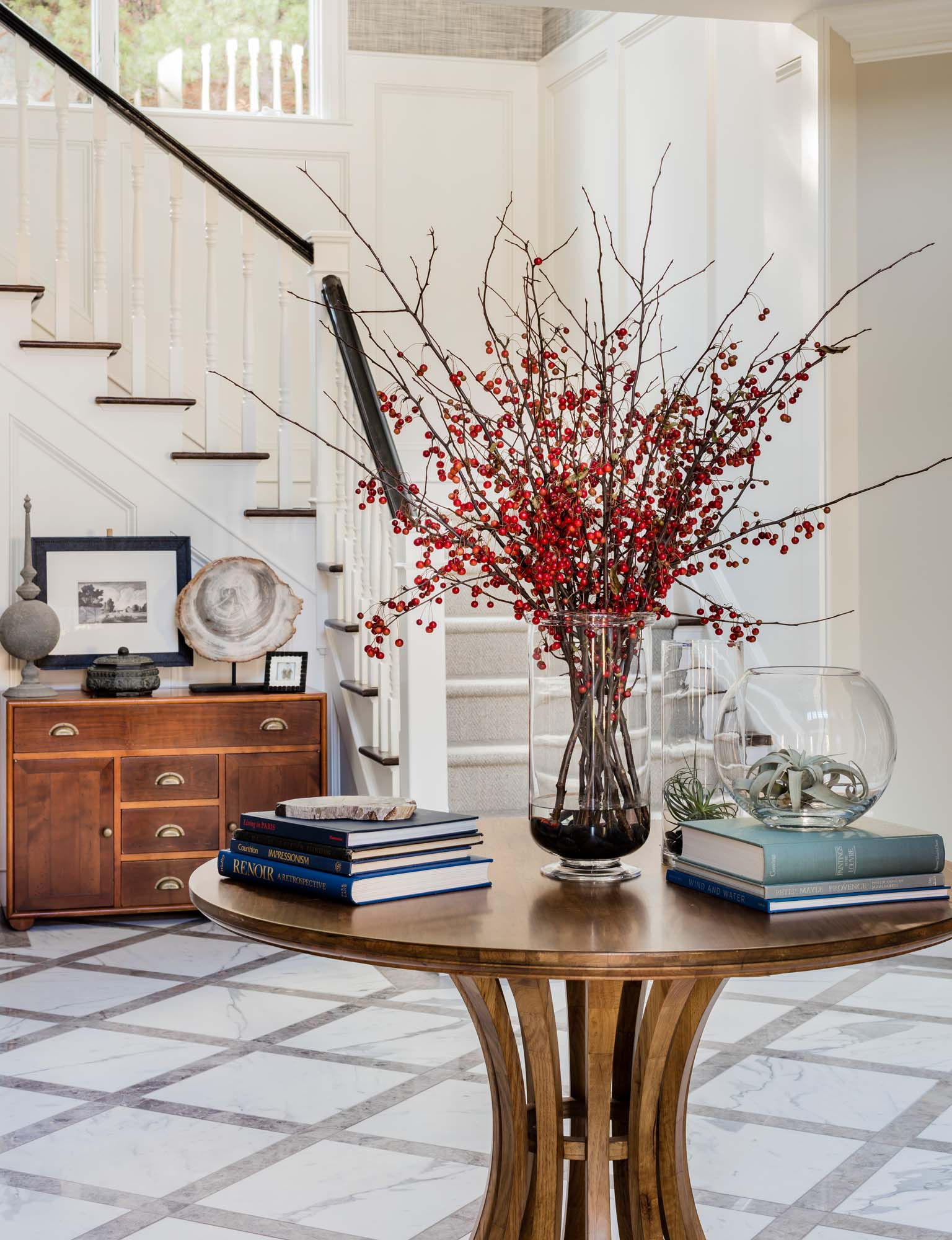 House interior with round wooden table, books, staircase and wooden drawer, statuary marble, honed statuary marble, grange chest, grange commode, red berries, air plant, air plants,