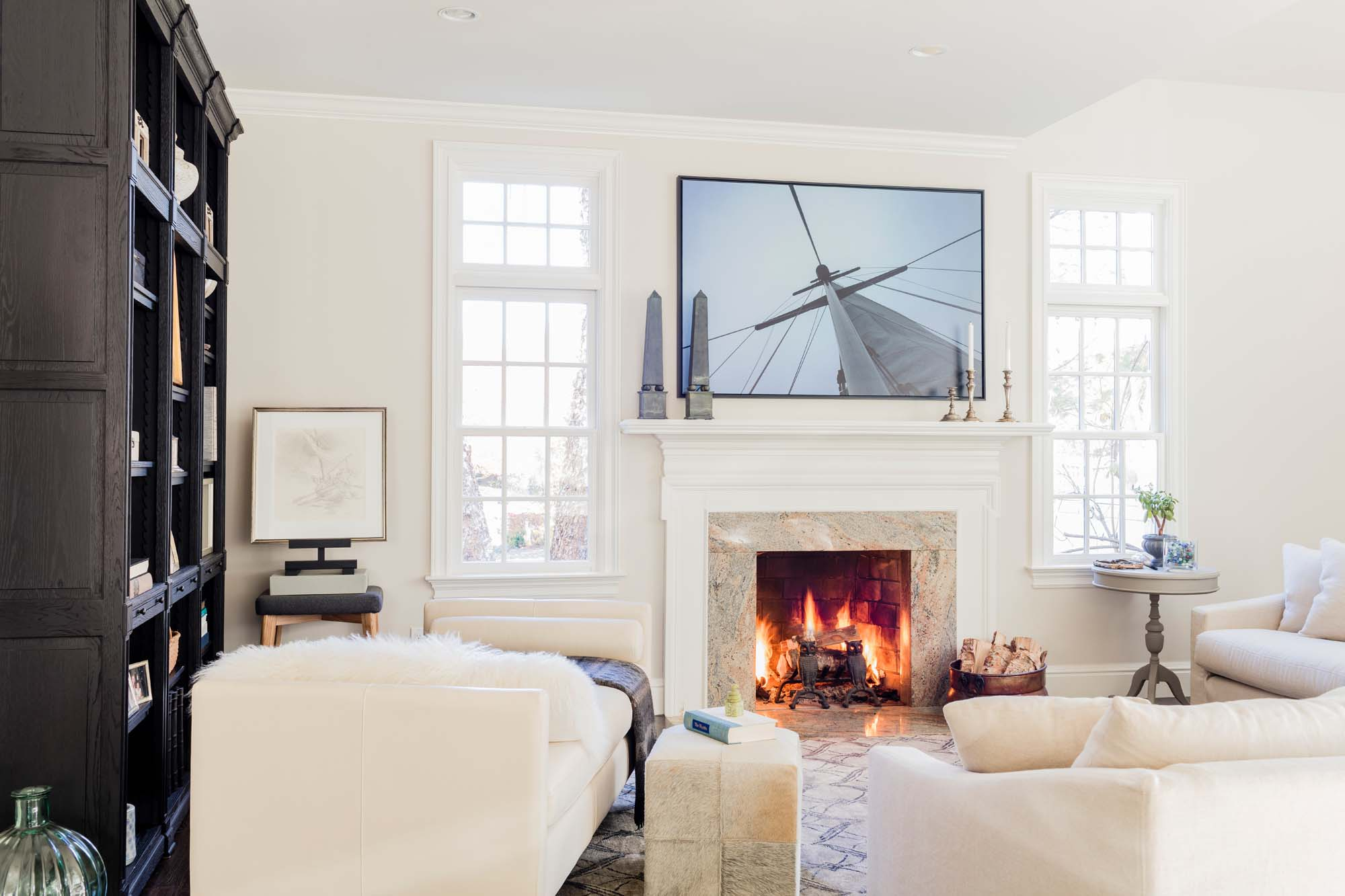 Living room with white sofa, white painted walls, white window frame and a wooden shelves — day bed, verellen, verellen sectional, duke, sectional, room and board day bed, original artwork, art, photograph, nautical, fireplace, obelisk, rh, restoration hardware, black oak, black wood, white dove, benjamin moore, winds breath, wind's breath