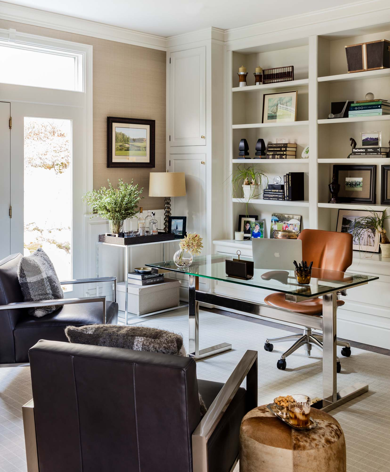 House interior with arm chairs, glass table, office chair and shelves, eames chair, glass desk, williams sonoma, bar, leather chair, room and board, silk wallpaper, winfield thybony, dark floor, stained floor, benjamin moore, white dove, sea pearl, seapearl, balboa mist,