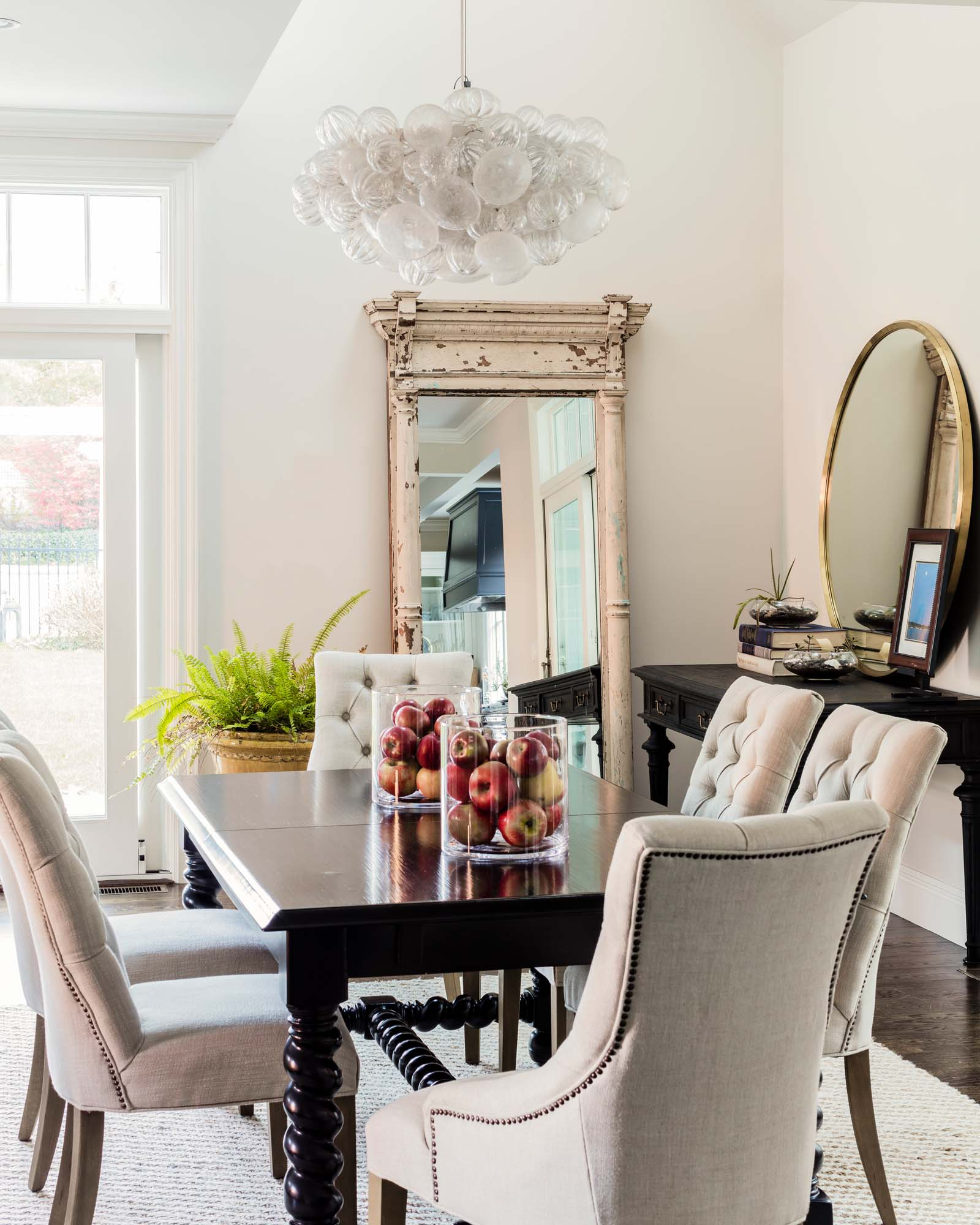 Dining room with wooden table, chairs, white painted walls and vintage mirror, williams sonoma table, rh, restoration hardware, martine, martine chair, apple, red apple, french planter, brim field, black oak, custom light, glass bubble, jute rug, wool rug