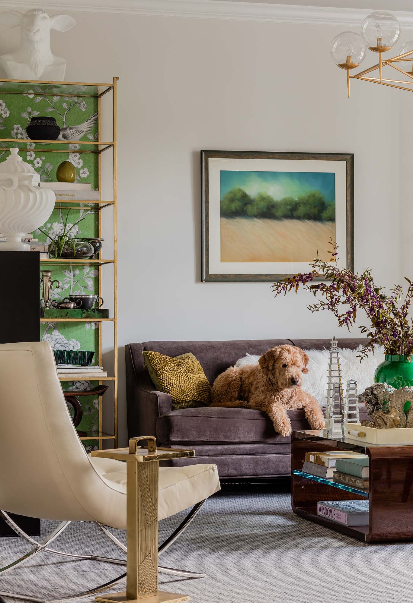 Living room with sofa, shelves, center table, and artwork on the wall, goldendoodle, golden doodle, mary McDonald, chinoiserie, herringbone, herringbone rug, gray sofa, velvet sofa, dragon, chinois palais, lettuce green, obelisk, williams sonoma, james chair, white leather, rowan, worlds away, chandelier, delano, etagere, currey, currey and company, plinth, oly studio, ramsey, animal bust