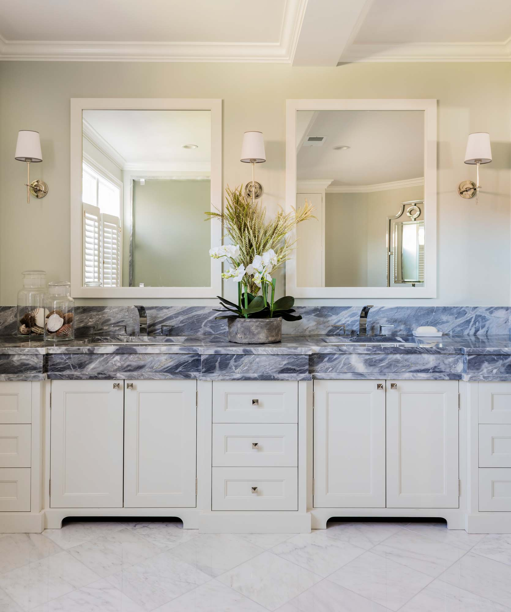 Bathroom with ceramic countertops, white wooden cabinets, and mirrors on the wall, not ceramic countertop, calcutta gray marble, gray marble, calcutta, custom countertop, custom cabinet, white dove, benjamin moore, visual comfort, bryant sconce, polished nickel, rohl faucet, wave faucet, arebescato, marble, arebescato marble, 12 inch
