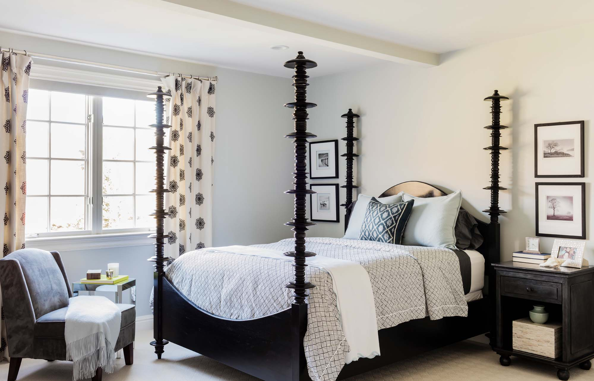 Bedroom with wooden bed, bedside table, chair, and frames on the wall, anthropologie, black bed, matouk, matouk bedding, black and white, guest bedroom