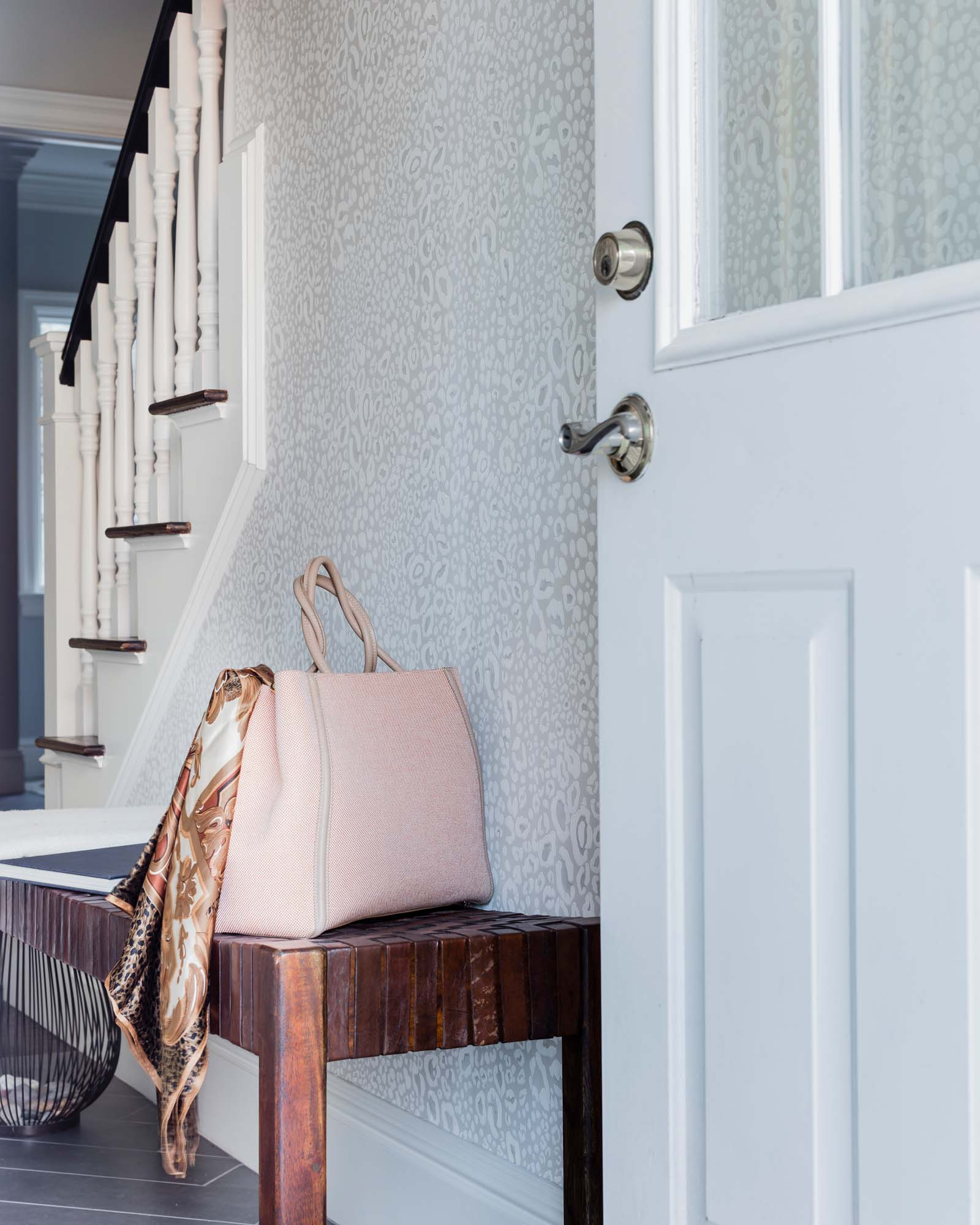 House interior with white wooden door, wooden table, and stairway, leather bench, farrow and ball, wallpaper, ocelot, fendi, purse, handbag