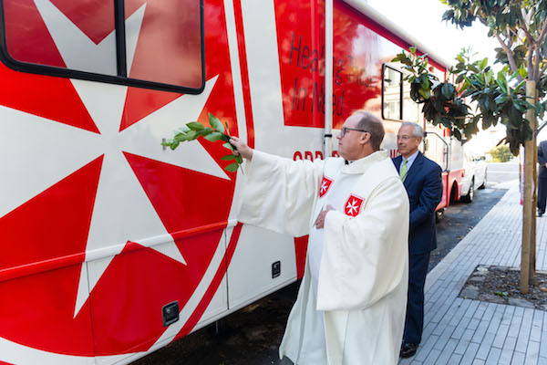 SAN FRANCISCO, CA – June 20 – New Mobile Unit for Sick and Uninsured Blessed by Fr. Eric Hollas and Ready for Bay Area Launch. Bill Cumbelich in the background holds holy water.