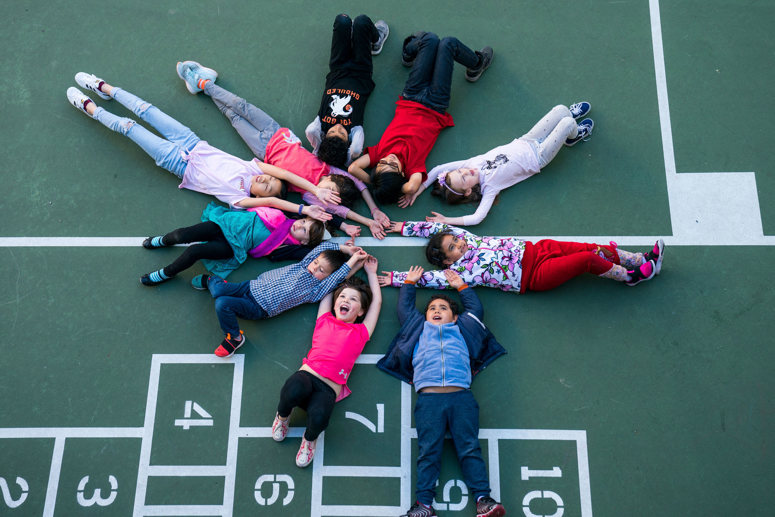 Children laying in a circle on the playground