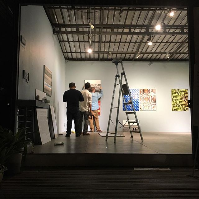 Tonight in Chiang Mai at @galleryseescape.official, we wandered down and found an artist, his curator and his gallerist up past dinner sorting out their hang for tomorrow's opening. #artislife #chiangmaicreativecity #notwavingbutdrowning #southeastasia