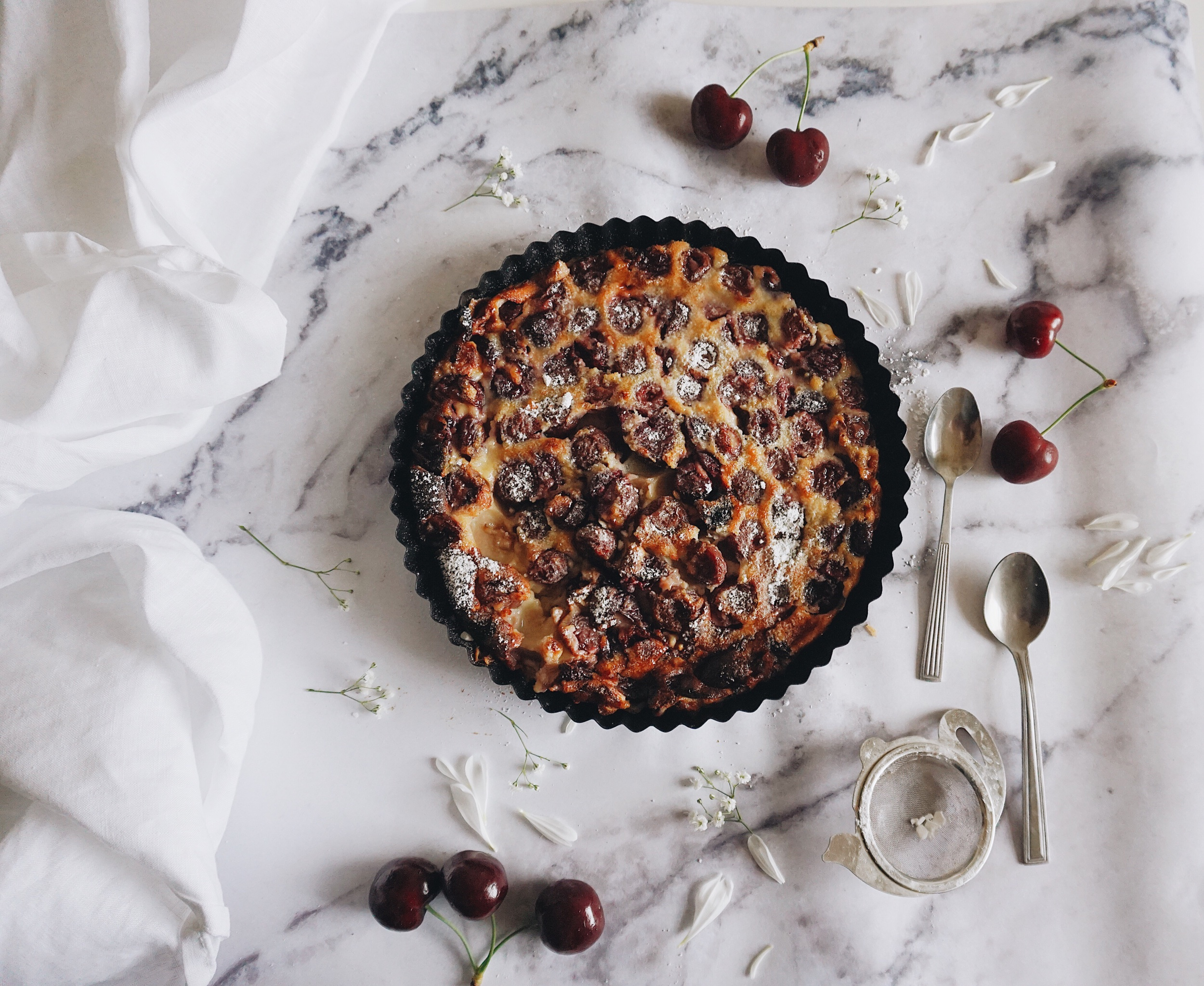 cherry almond clafoutis perfect summer dessert cracked custard top dusted with icing sugar surrounded by summer flowers and red cherries